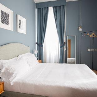 Immagine di una piccola camera matrimoniale contemporanea con pareti blu, pavimento marrone, nessun camino e pavimento in legno massello medio