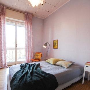 Immagine di una camera matrimoniale nordica con pavimento in legno massello medio, pareti viola e pavimento marrone