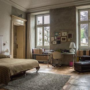 Foto di una camera da letto industriale con pareti grigie, pavimento in legno massello medio e pavimento marrone