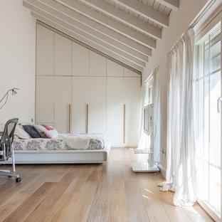 Immagine di un'ampia camera matrimoniale country con pareti bianche, parquet chiaro e pavimento beige
