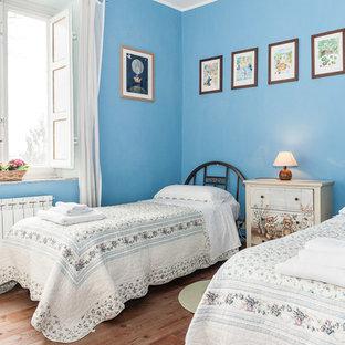 Foto di una camera degli ospiti mediterranea con pareti blu, pavimento in legno massello medio e pavimento marrone