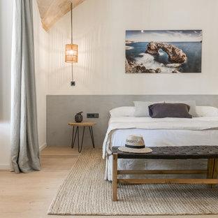 Immagine di una camera da letto mediterranea con pareti bianche, parquet chiaro e pavimento beige