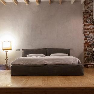 Foto di una camera padronale mediterranea di medie dimensioni con pareti bianche e parquet chiaro