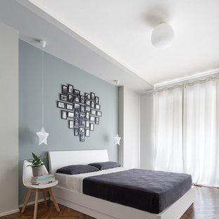 Diseño de dormitorio principal, actual, de tamaño medio, sin chimenea, con suelo de madera en tonos medios, paredes multicolor y suelo marrón