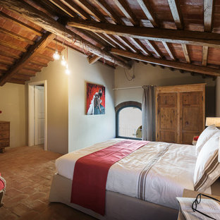 Bedroom - large farmhouse master terra-cotta floor and red floor bedroom idea in Florence with beige walls and no fireplace