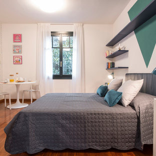 Design ideas for an expansive eclectic loft-style bedroom in Milan with blue walls and medium hardwood floors.