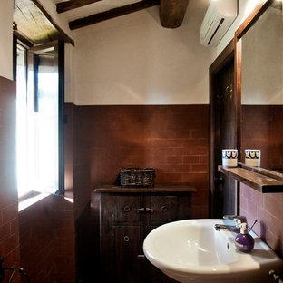 Foto de cuarto de baño con ducha, campestre, de tamaño medio, con armarios con paneles lisos, puertas de armario de madera en tonos medios, ducha empotrada, sanitario de dos piezas, baldosas y/o azulejos marrones, baldosas y/o azulejos de terracota, paredes blancas, suelo de baldosas de terracota y lavabo suspendido