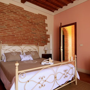 Mid-sized country guest bedroom in Other with pink walls, terra-cotta floors and brown floor.