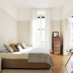 Idées déco pour une chambre parentale contemporaine de taille moyenne avec un mur gris, un sol en bois brun et un sol jaune.