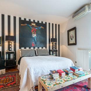 Foto di una camera matrimoniale mediterranea con pareti multicolore e pavimento in legno massello medio