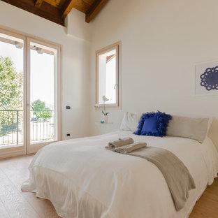 Foto di una camera da letto design con pareti bianche, parquet chiaro e pavimento beige