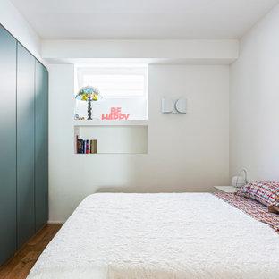 Foto de dormitorio principal, minimalista, grande, con paredes blancas, suelo de madera en tonos medios y suelo marrón