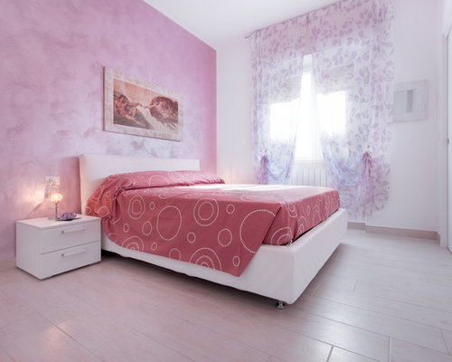 medium sized contemporary master bedroom in milan with pink walls
