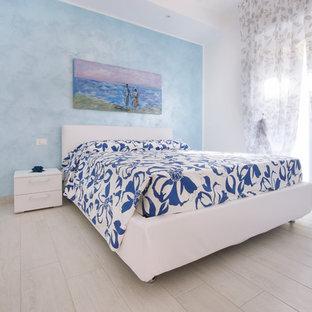 Esempio di una camera padronale al mare di medie dimensioni con pareti bianche