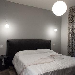 Immagine di una camera matrimoniale minimalista di medie dimensioni con pareti beige, pavimento in gres porcellanato e pavimento grigio