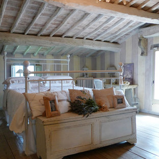 Imagen de dormitorio tipo loft, campestre, grande, con suelo de baldosas de terracota, estufa de leña y marco de chimenea de metal
