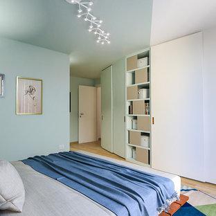 Immagine di una camera matrimoniale minimal di medie dimensioni con pareti verdi, parquet chiaro e pavimento marrone