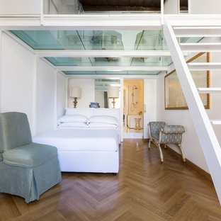 Traditional loft-style bedroom in Rome with white walls, laminate floors and brown floor.