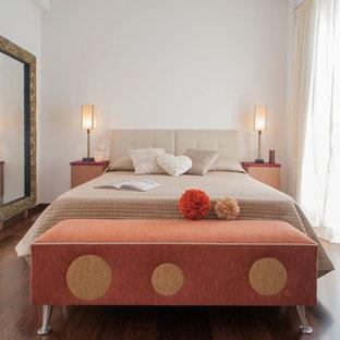 Immagine di una camera padronale minimal di medie dimensioni con pareti bianche e pavimento in legno massello medio
