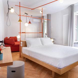 Immagine di una camera da letto minimal con pareti grigie, pavimento in legno massello medio e pavimento marrone