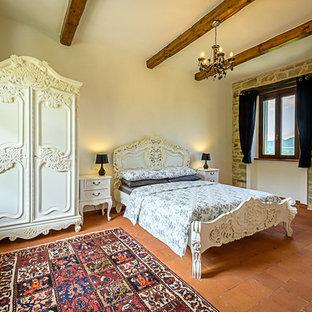 Immagine di una grande camera matrimoniale tradizionale con pareti bianche e pavimento in terracotta