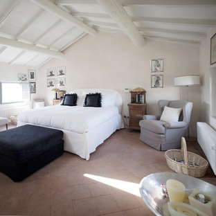 Inspiration for a large country master bedroom in Milan with beige walls and terra-cotta floors.