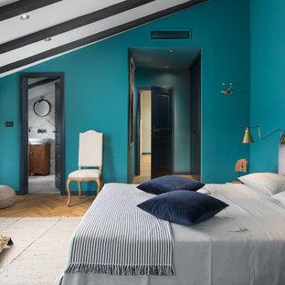 Exemple d'une chambre méditerranéenne avec un mur bleu, un sol en bois brun et un sol marron.