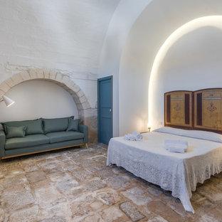Esempio di una grande camera matrimoniale mediterranea con pareti bianche, pavimento in pietra calcarea e pavimento beige