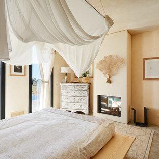 Foto di una camera matrimoniale tropicale con pareti beige, pavimento in cemento, camino classico e pavimento grigio