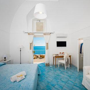 Modelo de dormitorio principal, marinero, de tamaño medio, con paredes blancas y suelo de baldosas de terracota
