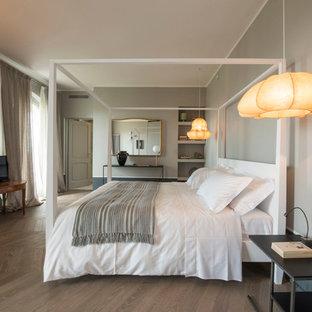 Idées déco pour une grande chambre parentale contemporaine avec un mur gris, un sol en bois foncé et un poêle à bois.