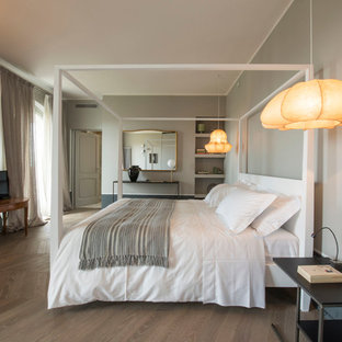 Идея дизайна: большая хозяйская спальня в современном стиле с серыми стенами, темным паркетным полом и печью-буржуйкой