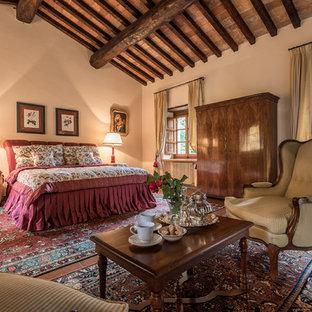 Ejemplo de dormitorio principal, campestre, extra grande, con paredes beige, suelo de baldosas de terracota, chimenea tradicional, marco de chimenea de piedra y suelo rojo