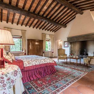 Ejemplo de dormitorio principal, de estilo de casa de campo, extra grande, con paredes beige, suelo de baldosas de terracota, chimenea tradicional, marco de chimenea de piedra y suelo rojo
