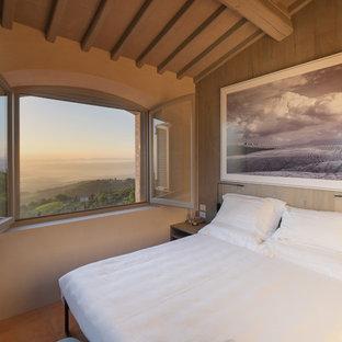 Idee per una camera da letto mediterranea con pareti beige, pavimento in terracotta e pavimento marrone