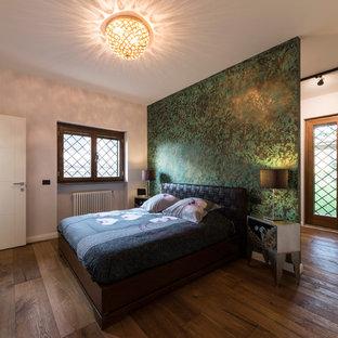 Foto di una grande camera matrimoniale minimal con pavimento in legno massello medio, pareti verdi e pavimento marrone
