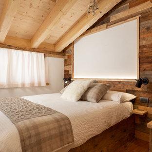 Immagine di una camera matrimoniale rustica con pareti marroni, pavimento in legno massello medio e pavimento marrone