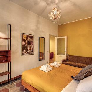 Foto de dormitorio principal, vintage, de tamaño medio, con paredes amarillas, suelo de cemento y suelo multicolor