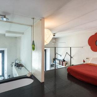Foto di una camera da letto stile loft minimal con pareti bianche, pavimento in vinile, pavimento nero e nessun camino