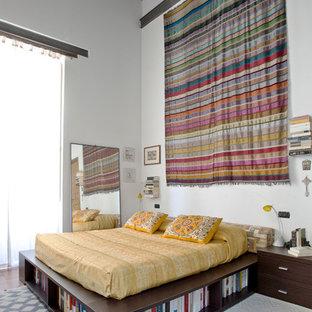 Immagine di una camera matrimoniale bohémian con pareti bianche e pavimento in terracotta