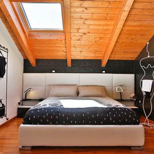 Idee per una camera matrimoniale design di medie dimensioni con pareti multicolore e pavimento in legno massello medio