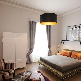 ローマの中くらいのコンテンポラリースタイルのおしゃれな主寝室 (白い壁、無垢フローリング、茶色い床) のインテリア