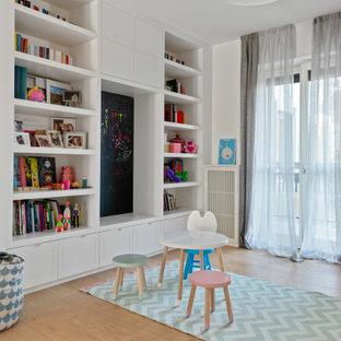 Immagine di una cameretta per bambini minimal con pareti bianche, parquet chiaro e pavimento beige