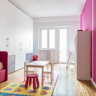 Esempio di una grande cameretta per bambini da 4 a 10 anni contemporanea con pavimento in legno massello medio, pavimento beige e pareti rosa