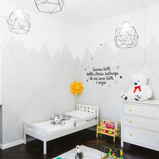 Medium sized traditional gender neutral toddler's room in Bologna with multi-coloured walls, dark hardwood flooring and brown floors.