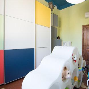 Ispirazione per una cameretta per bambini da 1 a 3 anni minimal di medie dimensioni con pareti multicolore e pavimento in terracotta