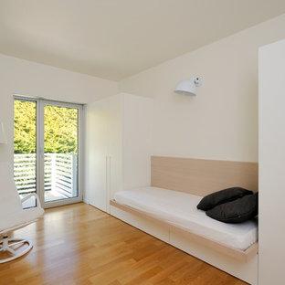 Foto på ett litet funkis könsneutralt tonårsrum kombinerat med skrivbord, med vita väggar, mellanmörkt trägolv och orange golv