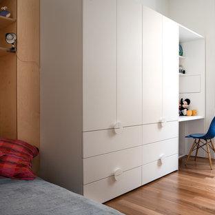 Ispirazione per una cameretta da letto contemporanea con pareti bianche, pavimento in legno massello medio e pavimento marrone