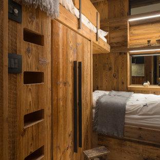 Пример оригинального дизайна: детская в стиле рустика с спальным местом, коричневыми стенами, паркетным полом среднего тона, коричневым полом и деревянными стенами