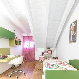 Immagine di una cameretta per bambini contemporanea con pareti bianche, pavimento in legno massello medio e pavimento marrone